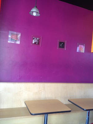 Interior photo of a birch wood bench and two yellow tables along our bright purple wall with small square framed photos of thai images