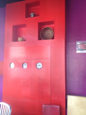 Interior photo of our bright red wall with thai art in 3 suare compartments in the wall